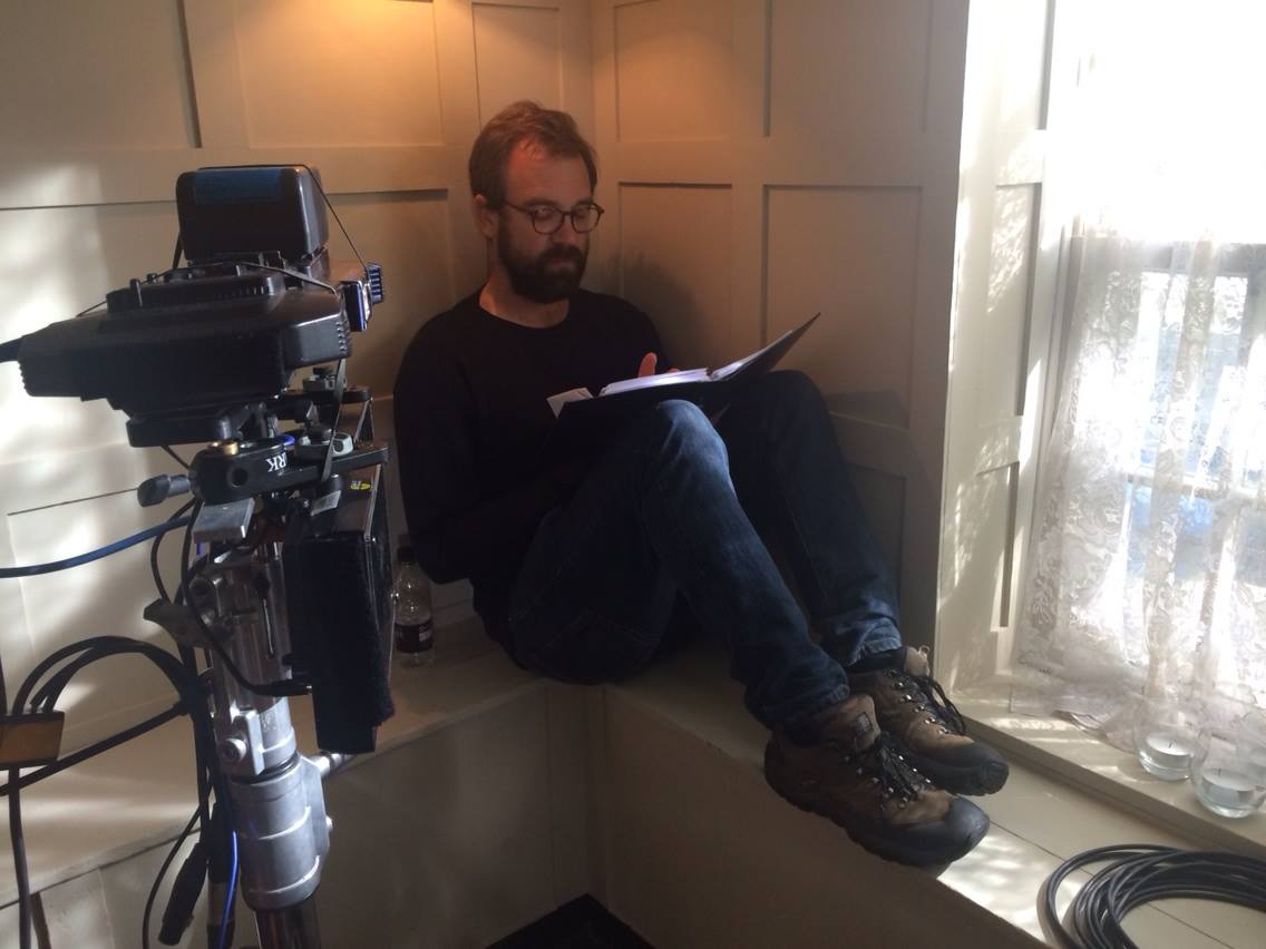 Director Adam Miller sits on a window sill reading his notes.