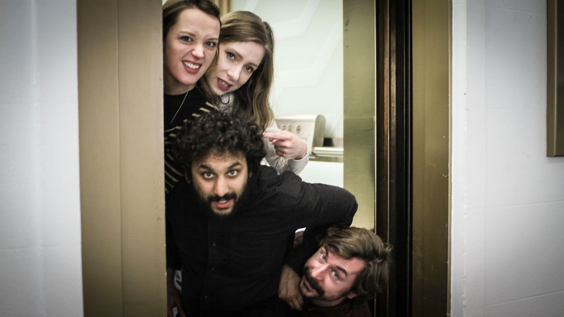Four comedians squash into a doorframe.