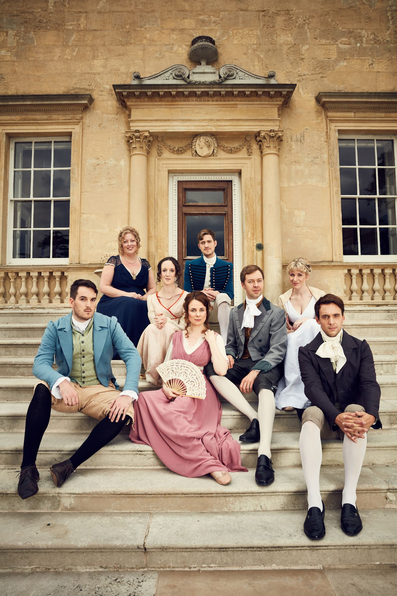 Eight performers in regency costumes sit on the steps of a large manorhouse.