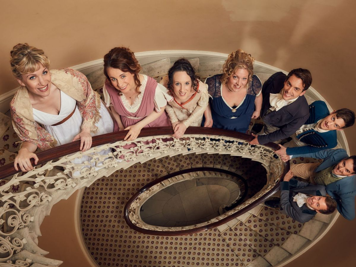 Eight performers in regency costumes line up on a spiral staircase.