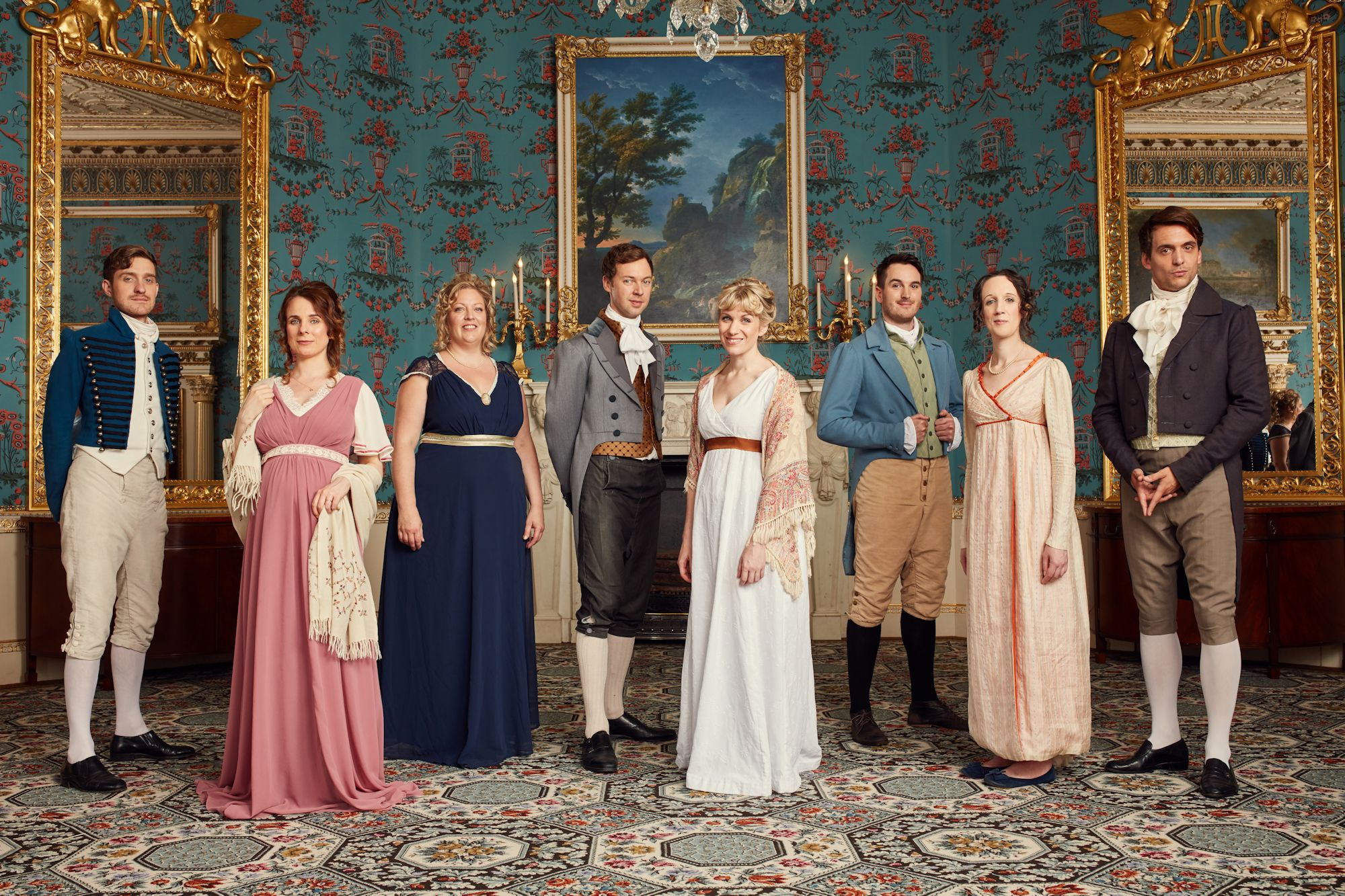 Eight performers in regency costumes line up in front of a painting in a large manor house.