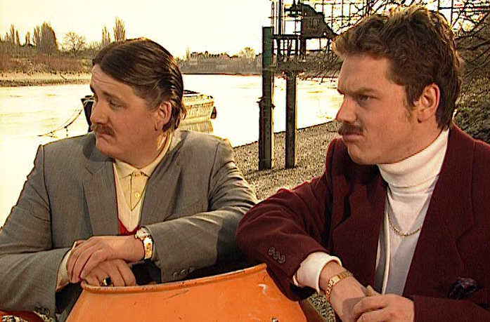 Two men in bad suits and fake moustaches stand on the side of a river, looking to the left.