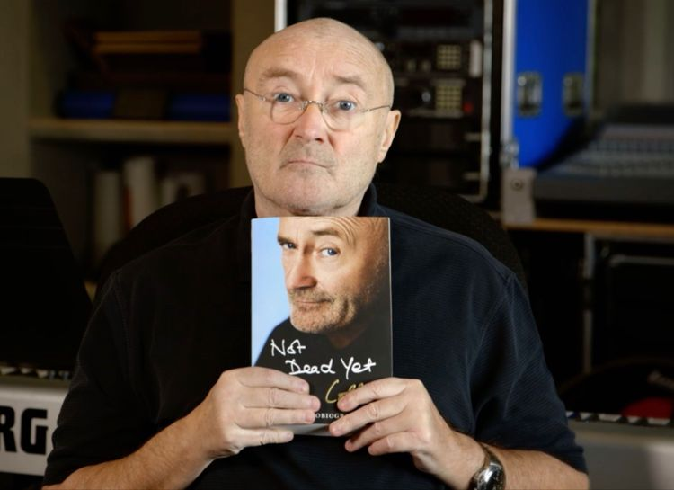 Phil Collins holds a copy of his autobiography in a recording studio