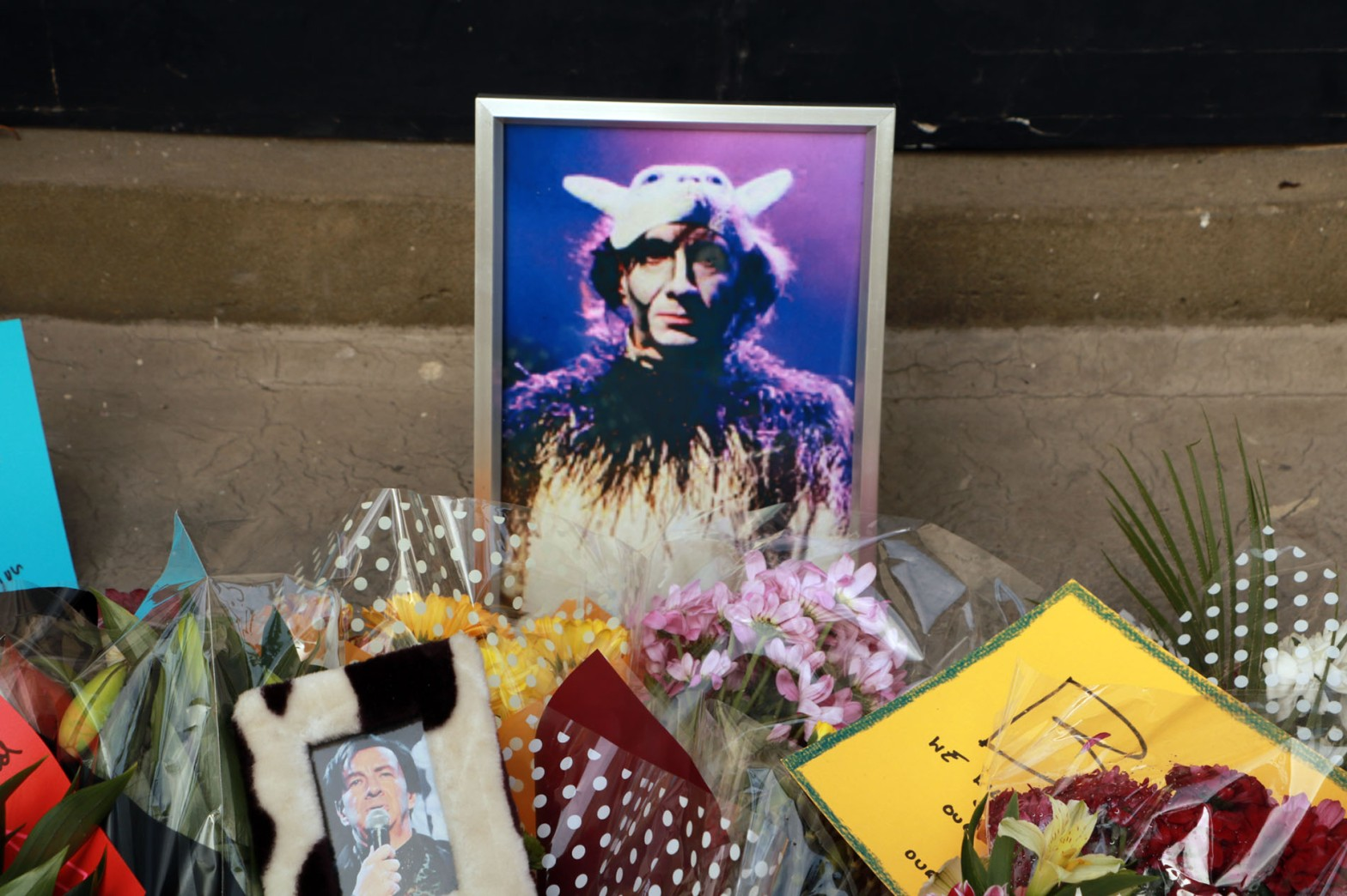 Photographs of Brian Pern surrounded by bouquets of flowers lie on the front steps of a house.