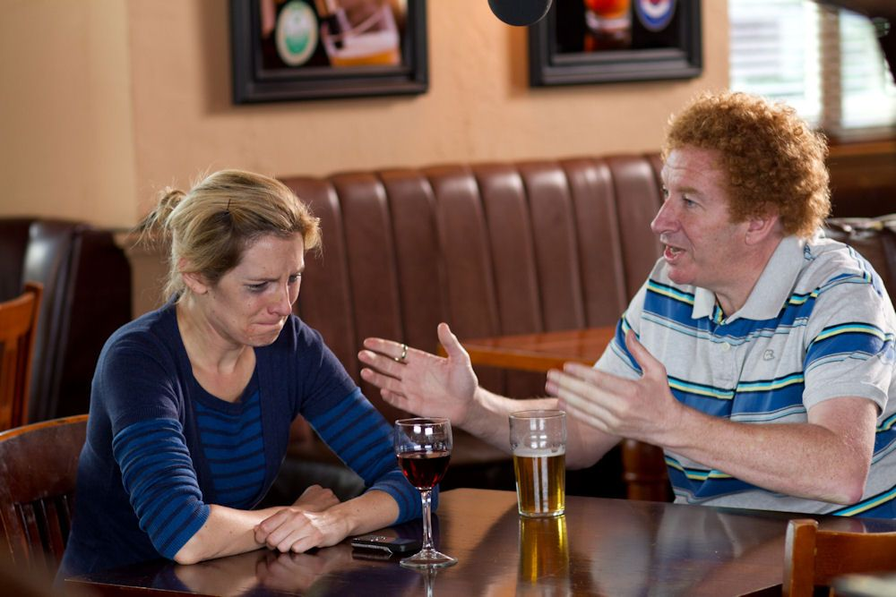 A woman with smudged makeup stares at a glass of wine in a pub, while a man sat beside her talks and waves his hands in the air.