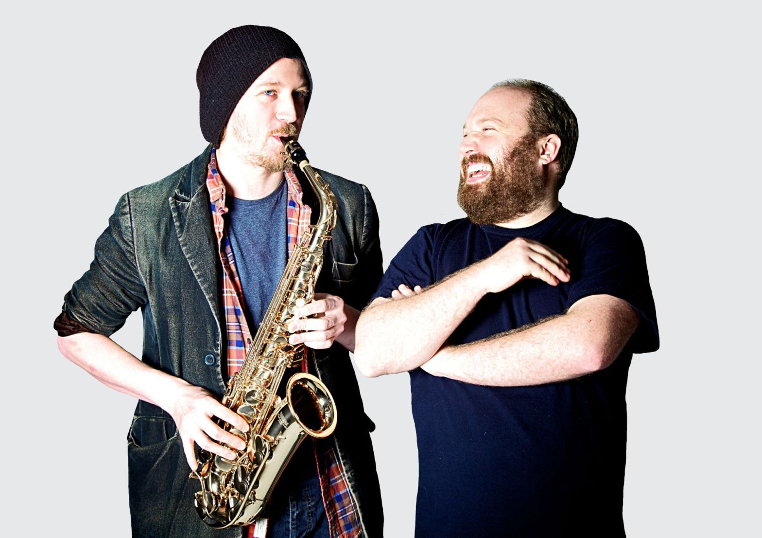 Paddy Gervers plays a saxophone while Jonny Donahoe laughs