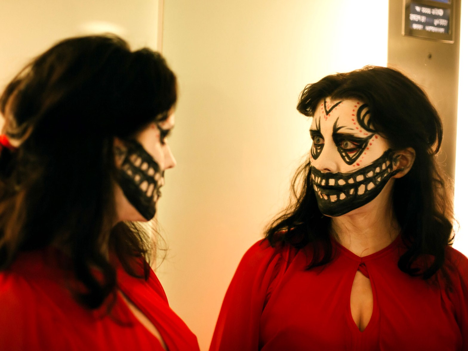 A woman wearing a red dress and skull face-paint, looks at herself in the mirror.