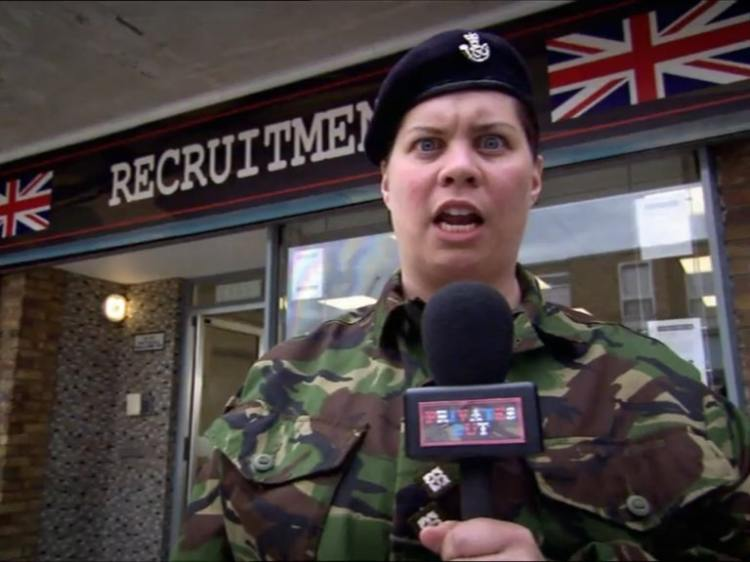 Katy Brand dressed as an army soldier in camo uniform, holding a microphone outside a Recruitment office.
