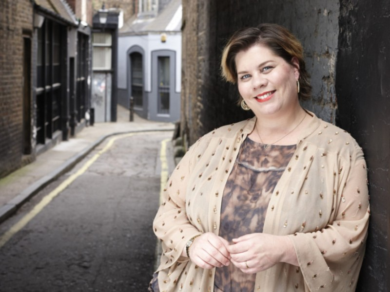 Katy Brand stands at the end of a narrow street.