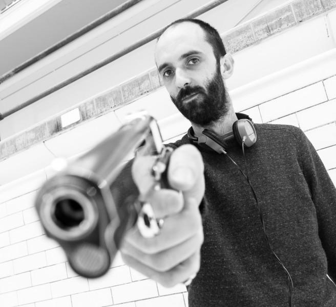 Director Dave Lambert poses with a gun.
