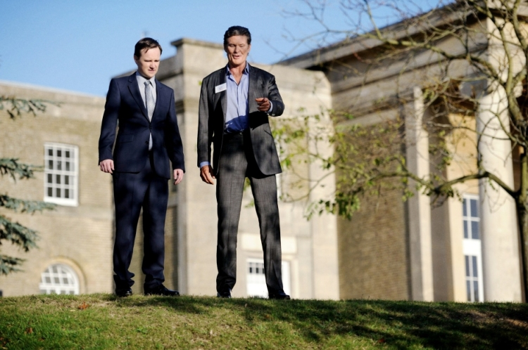 Fergus Craig and David Hasselhoff standing on a hill in front of a large house.