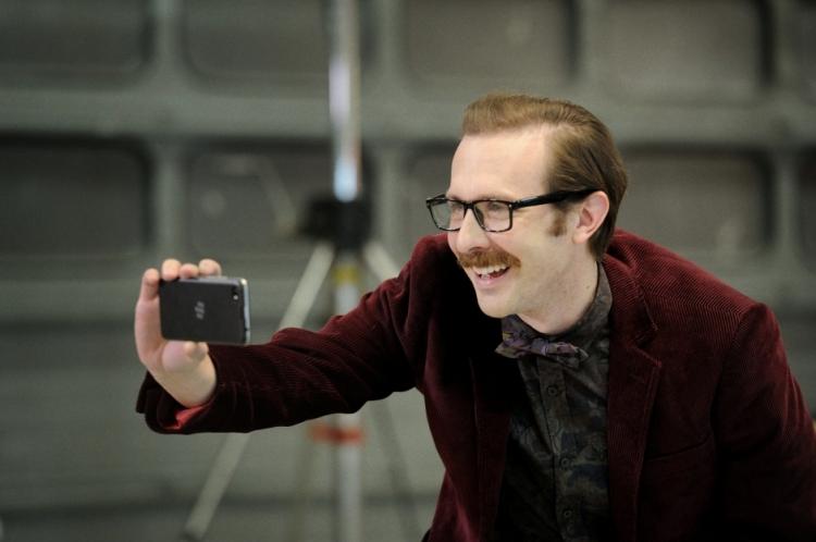 Tim Downie holding a camera phone.