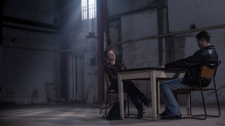 Sarah Alexander and Daniel Rigby sit either side of a table in a large warehouse.
